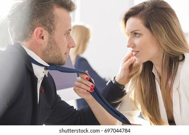 Woman touches blue tie of a man at work