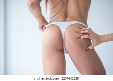 Woman touches the buttocks of a female body builder in white lingerie against a white wall. Female sports buttocks touches the female hand