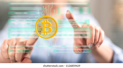 Woman touching a bitcoin currency concept on a touch screen with her fingers