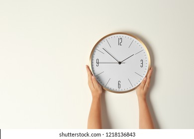 Woman touching clock on light wall, space for text. Time management