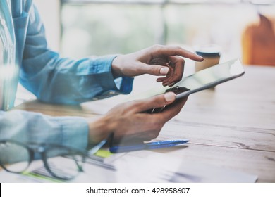 Woman Touching Digital Tablet Hand.Reflections Screen.Project Producer Researching Process.Young Business Crew Working with New Startup Studio. Blurred,film effect. Horizontal closeup photo