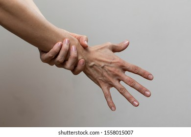 Woman touching forearm on grey background