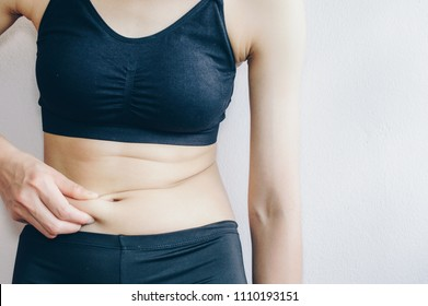 Woman touching her fat belly, woman's hand holding excessive belly fat.