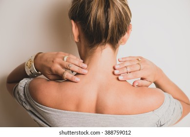 Woman touching her neck with her hands. She is wearing cool rings on her fingers.
