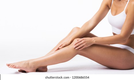 Woman touching her own legs on white background
