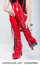 woman touching her red laquer knee high heels platform boots while lacing up. she is also wearing red latex leggings and a black red corset. she sits on a chair makes a string dominant expression.