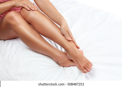 Woman touching her skin on her legs