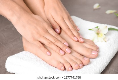Woman touching her smooth feet and towel on grey background, closeup. Spa treatment