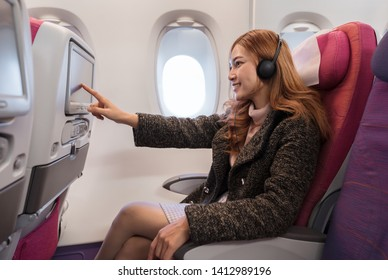 woman touching LCD entertainment screen on the airplane in flight time.