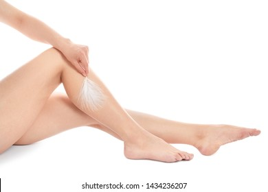 Woman touching leg with feather isolated on white, closeup. Epilation procedure