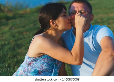 woman touching man's nose in sunset light