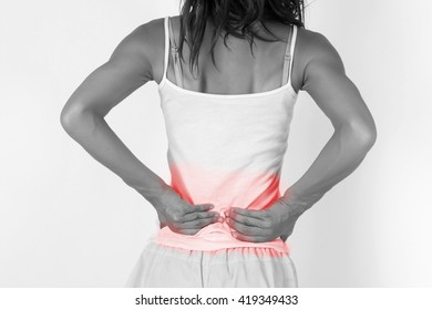 Woman touching painful back/spine. Pain in a woman back - healthcare concept