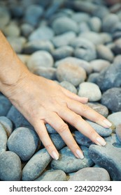 Woman touching pebbles, cropped view of hand