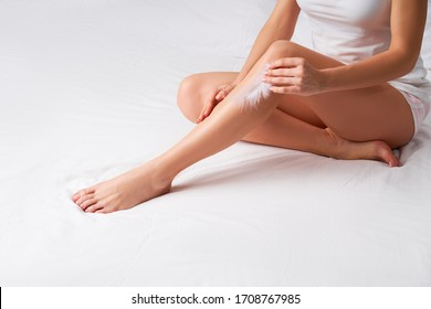 Woman touching smooth skin of her legs with feather in her hand