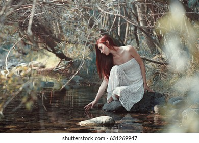 Woman touching water in a stream. Sunny woods