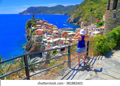 Woman tourist above historical town and harbor of Vernazza, Cinque Terre, Italy