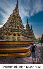 Woman Tourist admires beautiful architecture of Wat Pho Temple Bangkok Thailand