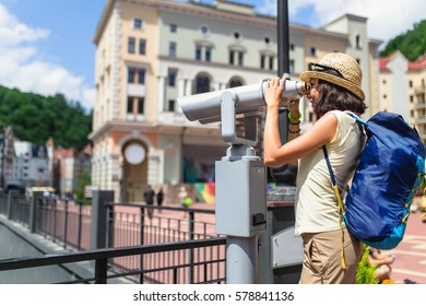Woman tourist admiring the views of the resort architecture of the city through a street telescope