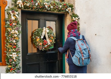 Woman tourist with a backpack knocking on a beautifully decorated New Year's door with a Christmas wreath