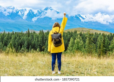 woman tourist with a backpack looks at the mountains in a conqueror pose.