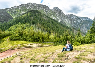 Woman tourist with backpack in mountains, view from peak of mountain in Tatras, summer landscape, Poland
