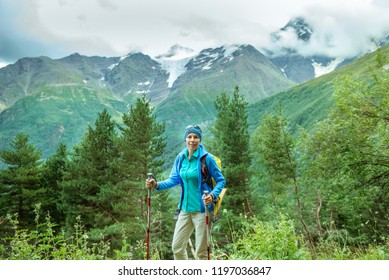 woman tourist with a backpack  using Nordic walking sticks while having an active weekend in the mountains
