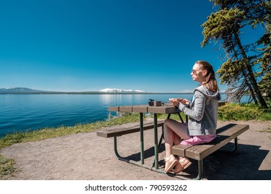 Woman tourist with camera having a breakfast by Yellowstone Lake, Wyoming, USA