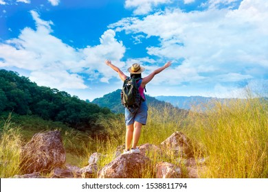 Woman tourist is carrying backpack standing on rock and spread her arms freely in the forest with mountainous. Concept of tourism and nature conservation.