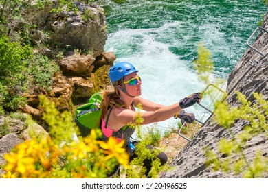 Woman tourist, with climbing gear, ascending on the via ferrata route in Cikola Canyon, on a hot, bright, Summer day, during a guided tour in Croatia.
