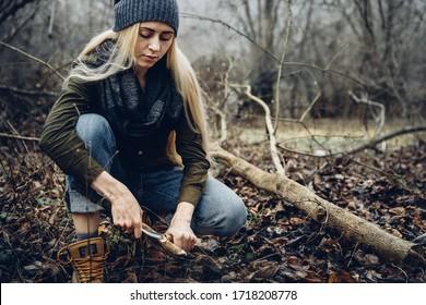 Une touriste coupe du bâton de bois avec un couteau dans la forêt. Concept de survie et de scoutisme des barges