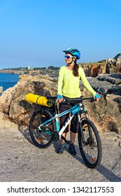 Woman tourist cyclist on the rocky shore on the lighthouse background. Portugal, Europe.