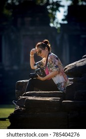 woman tourist with dslr camera in hand sitting on rock with beautiful sun light