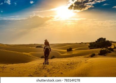 Woman tourist enjoy camel ride at the Thar desert Jaisalmer, Rajasthan at sunset.