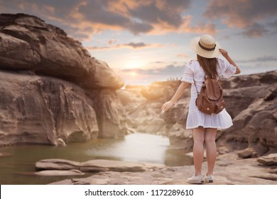 Woman tourist is enjoy sightseeing at Sam Phan Bok landscape view in Ubon Ratchathani, Thailand during sunset holiday vacation time.