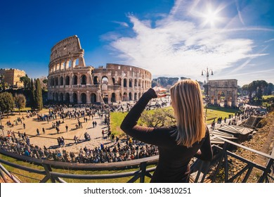 Woman tourist enjoying the view of the Roman Colosseum in Rome, Italy