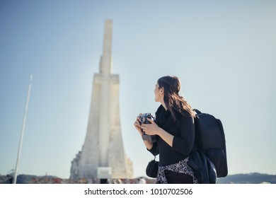Woman tourist at the famous Monument of Discoveries in Lisbon,Portugal.Visit site and viewpoint.Walking lane to the Belem tower.Budget traveling an free sightseeing.Travel photography.Europe trip