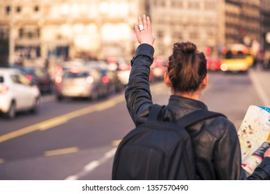 Woman tourist in a foreign city trying to hail a cab, holding a map to navigate herself
