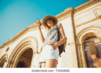 Woman tourist in hat with backpack using gps navigation on mobile phone. Summer fashion style. City tour. Explore world. Modern technology. Tourism concept. Yerevan. Bottom view. Wireless internet.