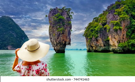 Woman tourist with hat and floral dress looking at James Bond island in Thailand