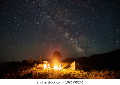 Woman tourist having a rest at night camping in the mountains under incredible beautiful starry sky and Milky way. Female backpacker sitting beside campfire and two tents. Astrophotography