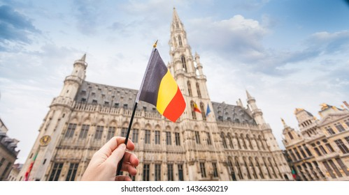 Woman tourist holds in her hand a flag of Belgium against the background of the Grand-Place Square in Brussels, Belgium. Traveling in Belgium, the main attraction of Brussels, the Grand Market Square