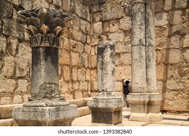 Woman tourist leans in doorway of archaeological ruins of synagogue at Capernaum, Israel