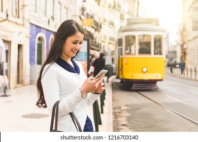 Woman tourist in Lisbon looking her smartphone and with famous yellow tram on background. Smiling happy young woman on the side of the street checking timetable on mobile phone. Travel in Europe.