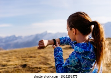 woman tourist looking at fitness bracelet on the background of mountains