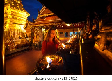 Woman tourist looking at prayer candle lights at Buddhist Temple Doi Suthep at night in Chiang Mai, Thailand