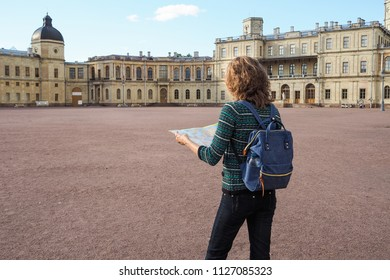 Woman tourist with map on the street. Travel guide, tourism in Europe. The ancient city of Gatchina