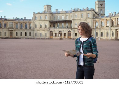 Woman tourist with map on the street. Travel guide, tourism in Europe. The ancient city of Gatchina.
