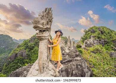 Woman tourist on background of amazing huge dragon statue at limestone mountain top near Hang Mua view point at foggy morning. Popular tourist attraction at Tam Coc, Ninh Binh. Vietnam travel