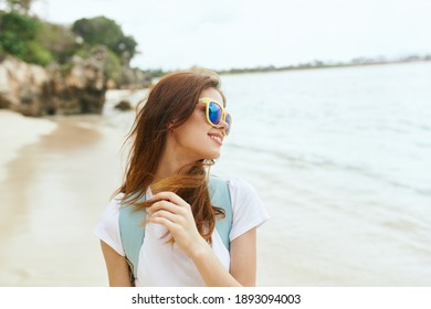 woman tourist on the beach near the sea looks to the side and palms in the background