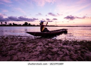Woman tourist on boat taking photo at the Sirindhorn Dam at Pattaya Noi (Little Pattaya) beach in Ubon Ratchathani.